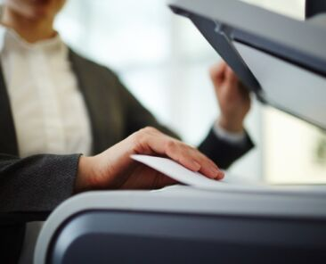 Secretary making copies or scanning papers on photocopier